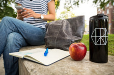 Student sitting next to an open textbook, an apple, and a water flask