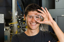 A young scientist looking through a lens